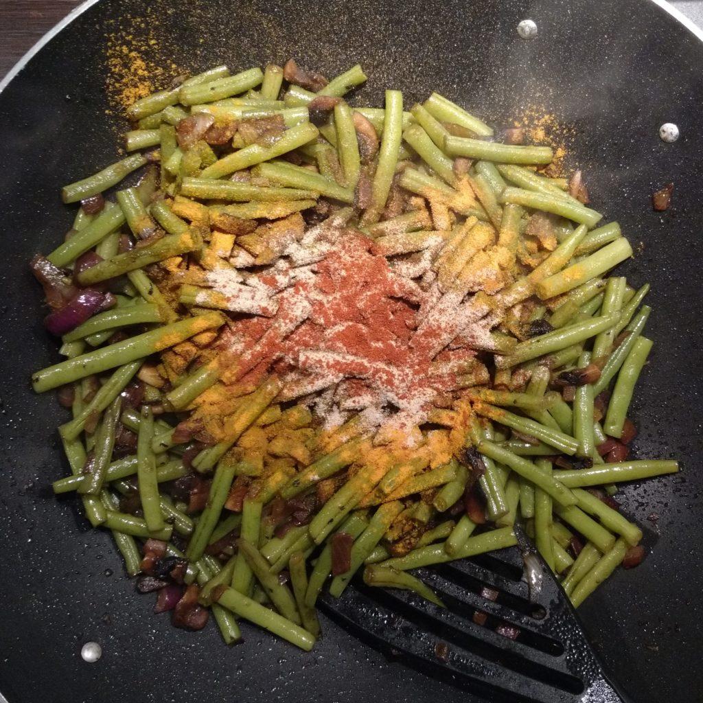 Kruiden toegevoegd aan de gewokte sperzieboontjes.